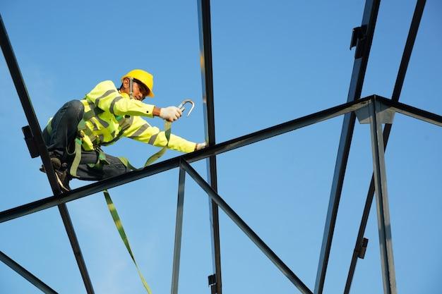건설 현장에서 높은 곳에서 작업하는 안전 장치 벨트를 착용하는 건설 노동자