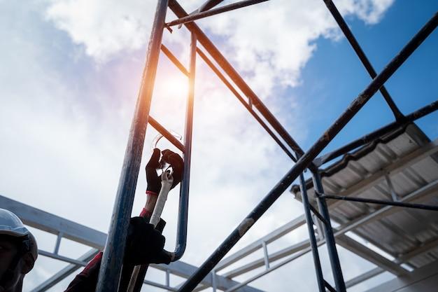 Строительные рабочие в ремнях безопасности, работающие на высоком уровне на строительной площадке, кровельные инструменты, электрическая дрель, используемые на новых крышах с металлическим листом.