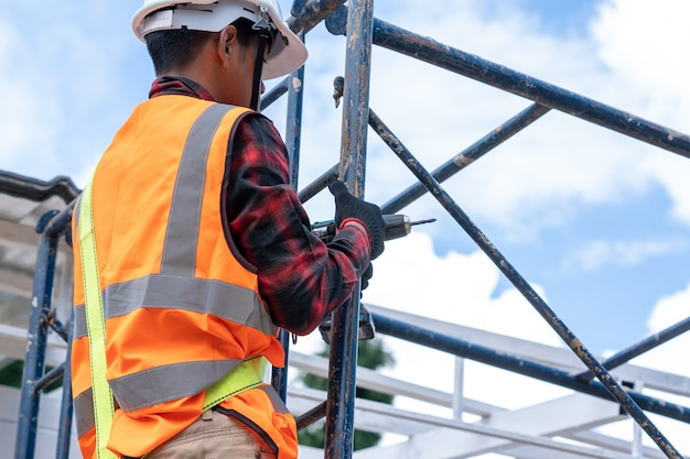 건설 현장에서 높은 수준에서 작업하는 안전 장치를 착용한 건설 노동자, 지붕 도구, 금속 시트가 있는 새 지붕에 사용되는 전기 드릴.