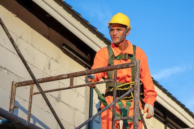 Строительные рабочие носить страховочную веревку во время работы на строительной площадке.