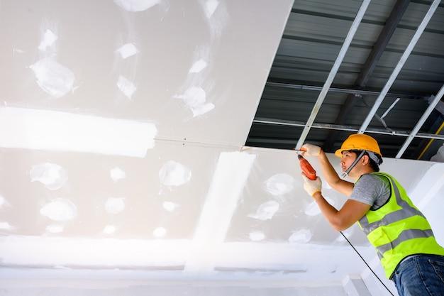 制服を着た建設作業員家や建物の中に石膏天井を設置します。電動ドライバーを使用して天井を取り付けます。