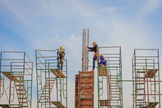 Construction workers working on scaffolding at a high level include a safety belt for safe