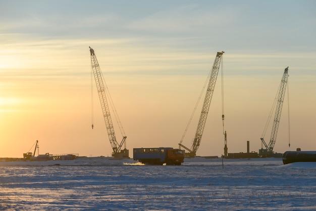 겨울 툰드라에서 공사가 진행됩니다. 사람들과 함께하는 특별한 버스. 댐 건물, 크레인, 바지선, 준설선.