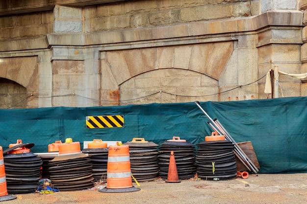 Зона строительства с оранжевыми маркерами осторожности вдоль городской улицы. дорожные работы