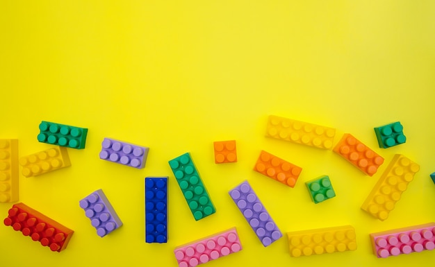 Constructor details are scattered on a yellow background. multi-colored construction blocks.