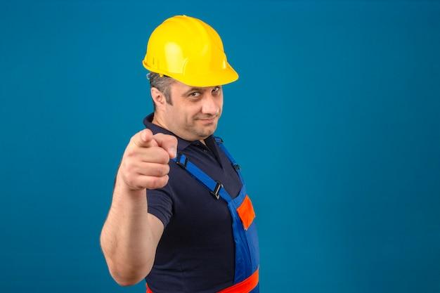 Строитель средних лет в строительной форме и защитном шлеме, счастливо улыбаясь и указывая указательными пальцами на камеру над изолированной синей стеной