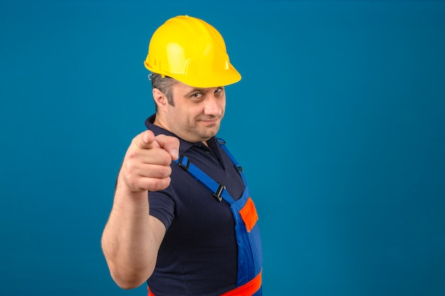 Constructor middle aged man wearing construction uniform and safety helmet smiling happily and pointing his index fingers at camera over isolated blue wall