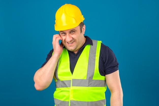 Строитель средних лет в строительном желтом жилете и защитном шлеме, царапающий лицо, замышляя что-то хитро улыбаясь, имеет интересную идею над изолированной синей стеной