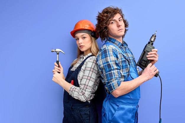Constructors builders stand back to back to each other holding household tools