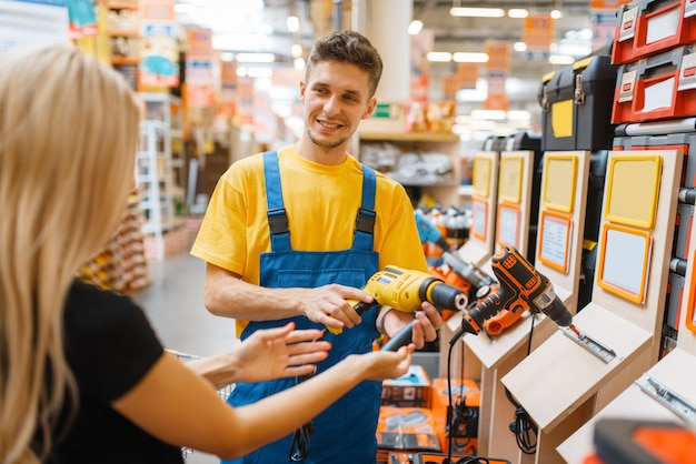 Consultant and female consumer in hardware store. seller in uniform and woman in diy shop, shopping in building supermarket