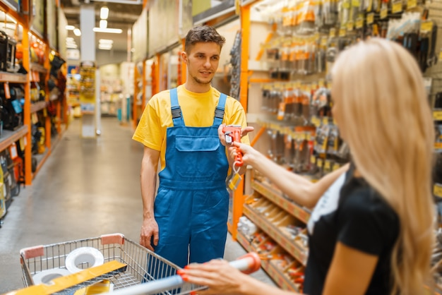 Consultant and female purchaser in hardware store. seller in uniform and woman in diy shop, shopping in building supermarket