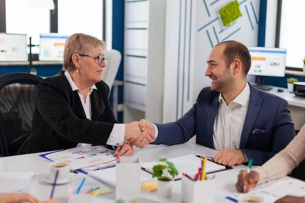 Consultant greeting international client with handshake after planning partnership deal
