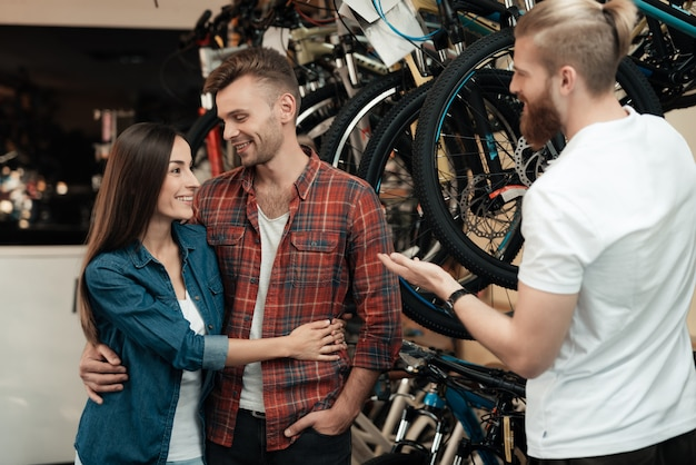 Consultant helps young couple in bike choosing.