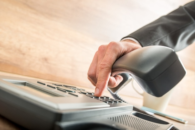 Consultant holding the receiver of a corded desk phone while dialing, in the office.