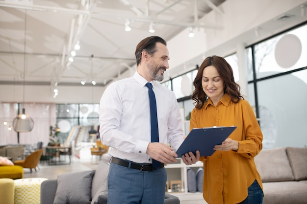 Консультант мебельного магазина показывает прейскурант новому клиенту