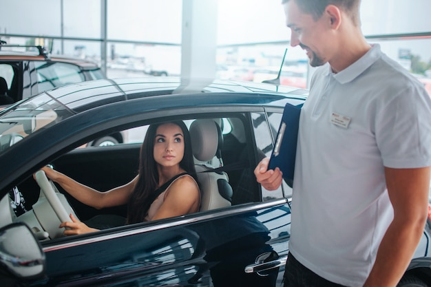 흰 셔츠에 컨설턴트 차 외에 서 있고 젊은 여자를 본다