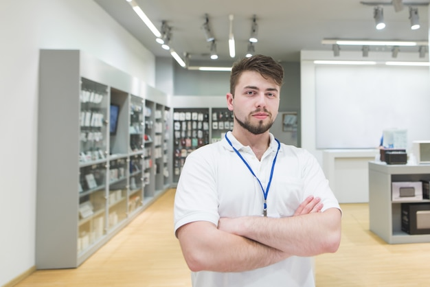 Consultant poses to the camera on a light electronics store.