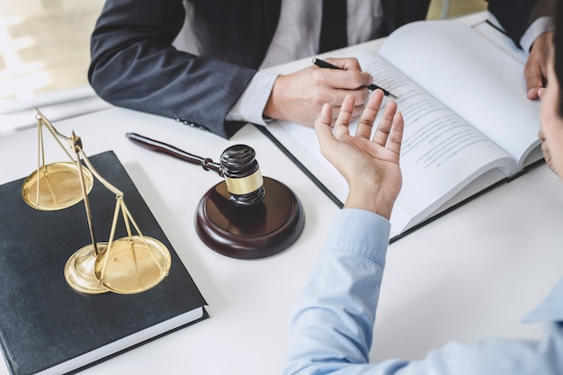 Consultation and conference of male lawyers and professional businesswoman working and discussion having at law firm in office. concepts of law, judge gavel with scales of justice