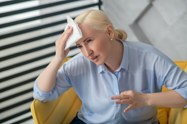 Consultation, health. adult fair-haired woman with a napkin near her forehead sitting telling about feeling ill, sad.