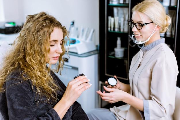 美容クリニックでの相談。女性患者と話して、スキンケアと治療のための新しいクリーム化粧品を示す女性美容医師。