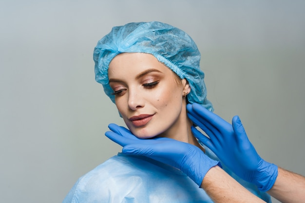 Consultation with plastic surgeon on white surface