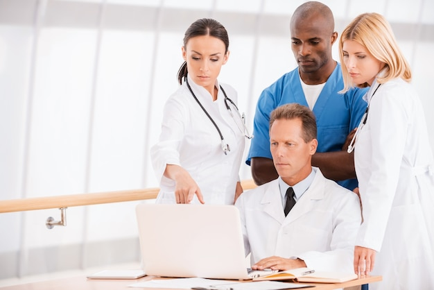 適切な治療についての相談。ラップトップを一緒に見ながら何かについて話し合う自信のある医師のグループ