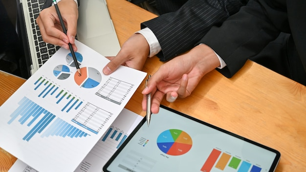 Consulting business with two man analysis finance data with device and paper document.