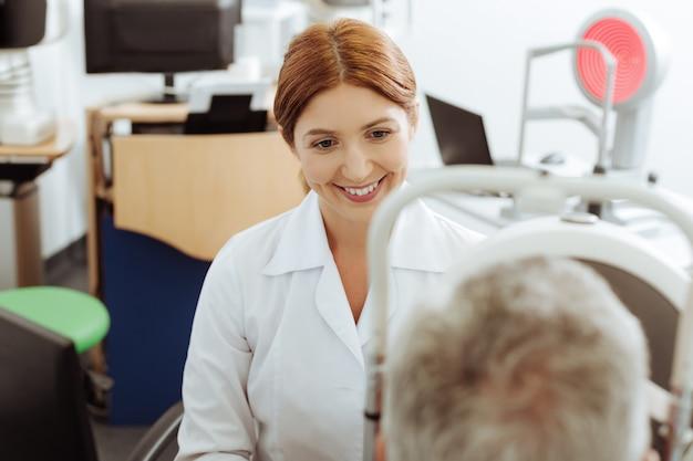 Консультант. сияющий глазной врач в белом халате сидит возле ноутбука во время консультации с мужчиной
