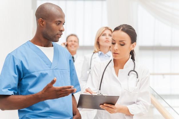 이동 중에도 컨설팅합니다. 아래층으로 이동하는 자신감 있는 의사 그룹 중 두 명이 무언가를 논의하고 몸짓