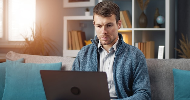 Consumed man using laptop holding it on his lap sitting on sofa in flat, e-work, diversion