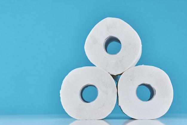 Покупательская паника по поводу концепции коронавируса ковид-19. рулоны туалетной бумаги на синем фоне. Premium Фотографии