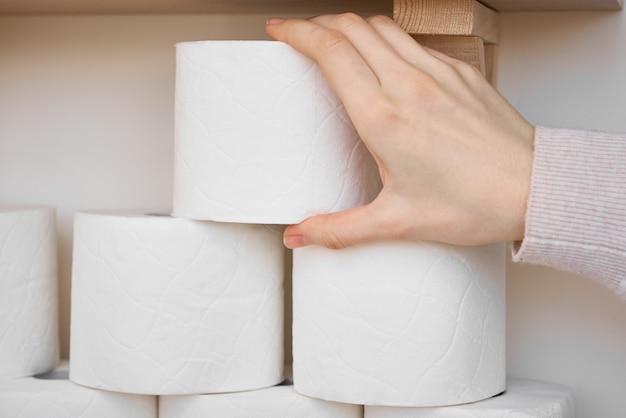 Покупательская паника по поводу концепции коронавируса ковид-19. женская рука берет туалетную бумагу woll с полки Premium Фотографии