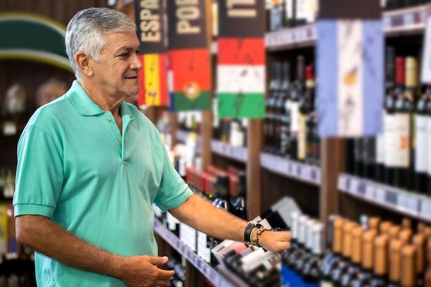Потребительский человек, выбирающий вина в супермаркете. бразильский мужчина.