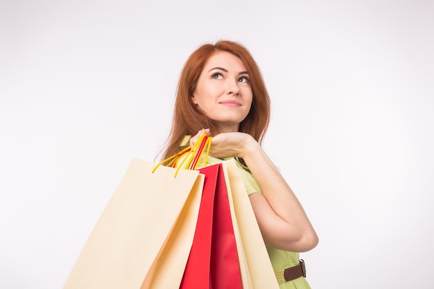 Consumer, sale and people concept - style redhead woman holding shopping bags