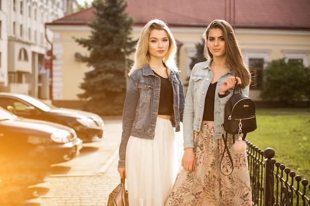晴れた姉妹女性が行く消費者の買い物