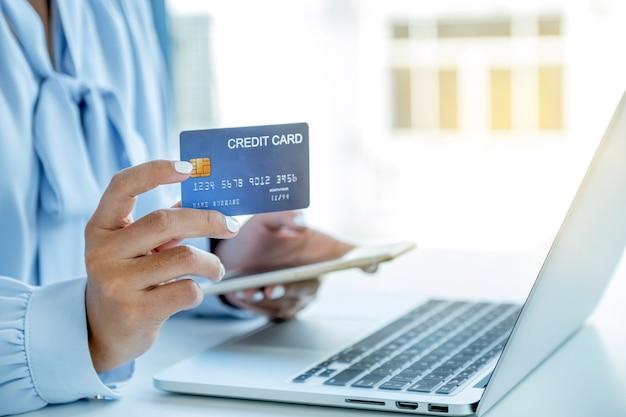 모의 신용 카드를 들고 있는 소비자 여성, 홈 오피스에서 노트북을 통해 할인 제품에 따라 온라인 금융 쇼핑을 할 준비가 되었습니다.