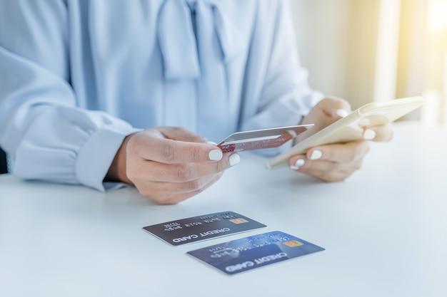 신용 카드를 들고 있는 소비자 여성은 홈 오피스에서 스마트 폰을 통해 할인 제품에 따라 온라인 금융 쇼핑을 할 준비가 되어 있습니다.