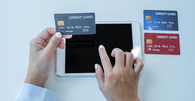 가정 사무실에서 태블릿을 통해 할인 제품에 따라 온라인 금융 쇼핑을 할 준비가 된 모의 신용 카드를 들고 있는 소비자 여성.