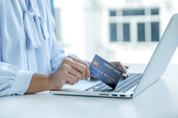 Женщина-потребитель рука держит макет кредитной карты, готовая тратить деньги на покупки в интернете