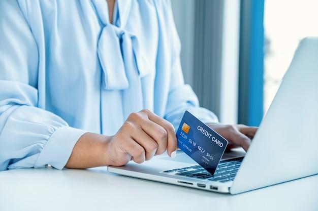 オンライン金融ショッピングを支払う準備ができてモックアップクレジットカードを持っている消費者女性の手