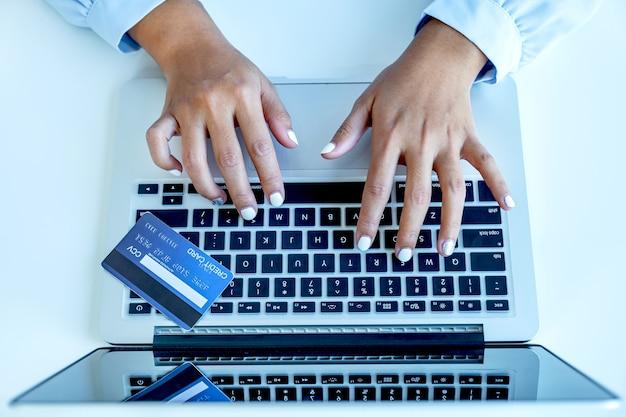소비자 여성은 노트북을 사용하고, 홈 오피스에서 노트북을 통해 할인 제품에 따라 신용 카드 지출을 온라인 금융 쇼핑으로 모의할 준비가 되었습니다.