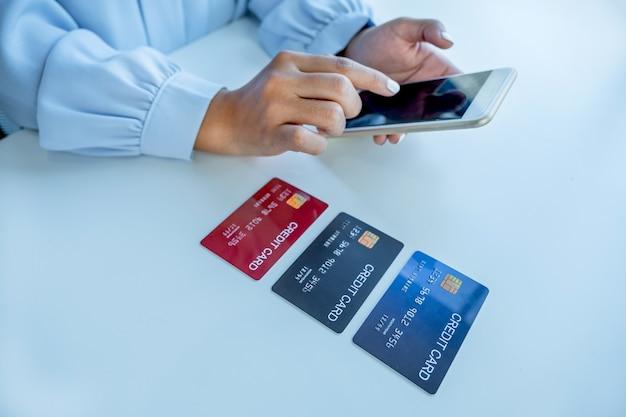 Женщина-потребитель рука использует смартфон и макет кредитной карты, готовая тратить деньги на покупки в интернете в соответствии со скидками из домашнего офиса.