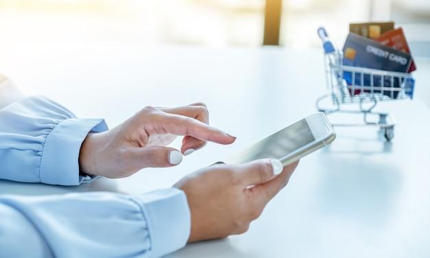 소비자 여성은 스마트폰과 모의 신용 카드를 사용하여 홈 오피스의 할인 제품에 따라 온라인 금융 쇼핑을 할 준비가 되어 있습니다.