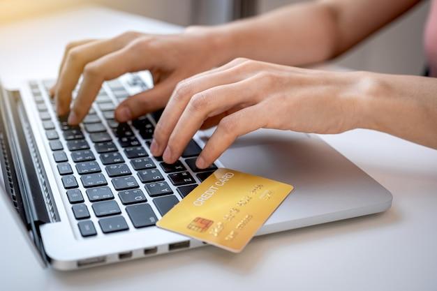 Рука женщины-потребителя, использующая ноутбук для покупок в интернете