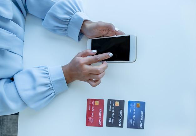 消費者の女性はスマートフォンを使用し、クレジットカードをモックアップしてオンライン金融ショッピングを支払う準備ができています