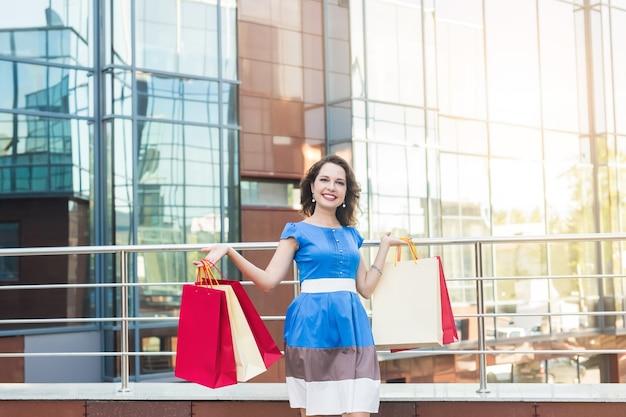 소비, 판매 및 사람들 개념. 따라 걷는 동안 쇼핑 가방을 들고 젊은 여자는