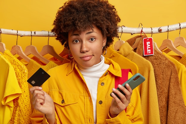 消費主義、ショッピング、ライフスタイルのコンセプト。知らない無知な縮れ毛の女性がクレジットカードと携帯電話を持っている