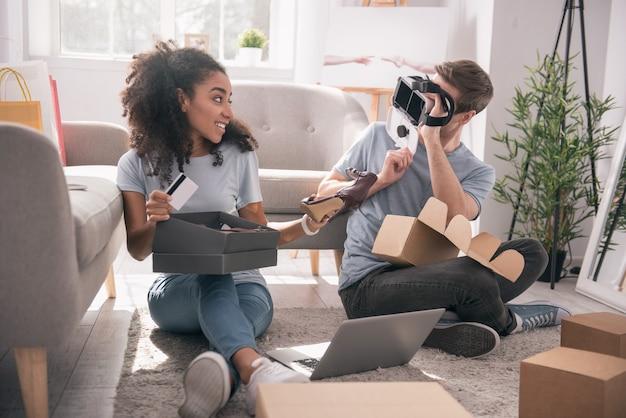 消費主義の傾向。彼らが買ったものを見ながら彼らのパッケージを開梱するうれしそうなポジティブなカップル