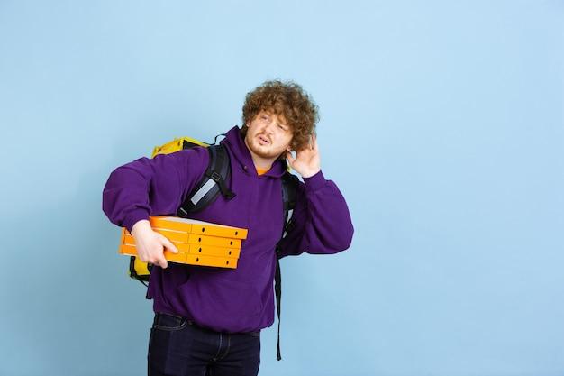 検疫中の無接触配達サービスは、青い壁に隔離された配達員の断熱感情の間に食べ物や買い物袋を配達します