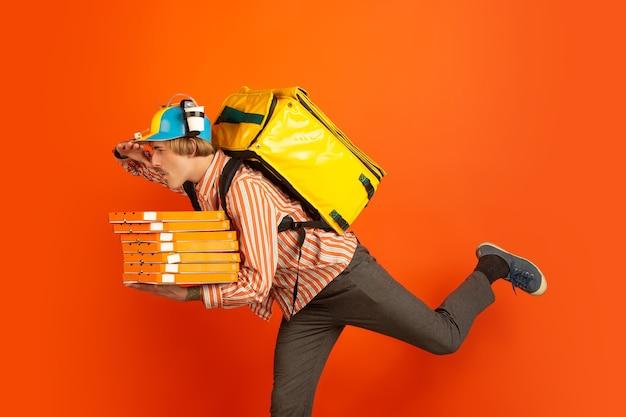 Бесконтактная доставка во время карантина. мужчина доставляет еду и пакеты с покупками во время утепления. эмоции доставщика, изолированные на оранжевом фоне.